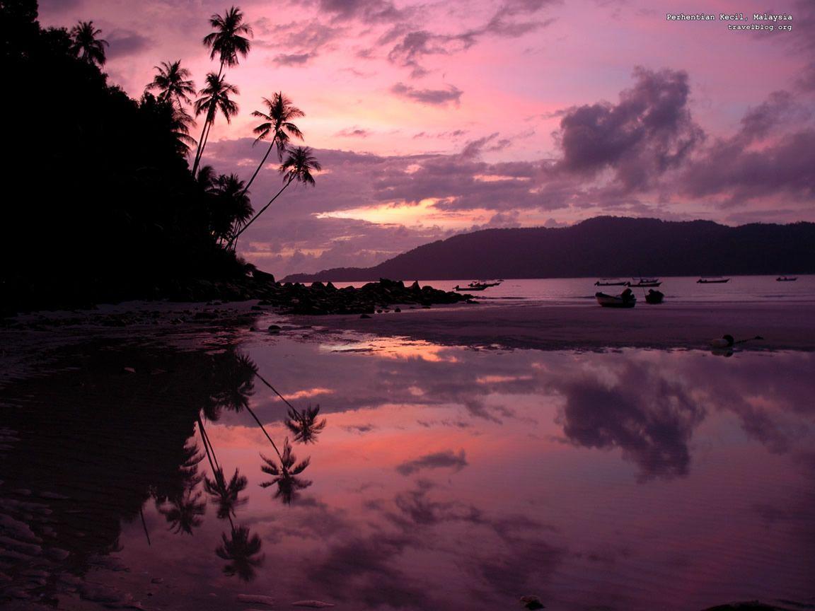 sun rising behind the blue sea wallpaper o