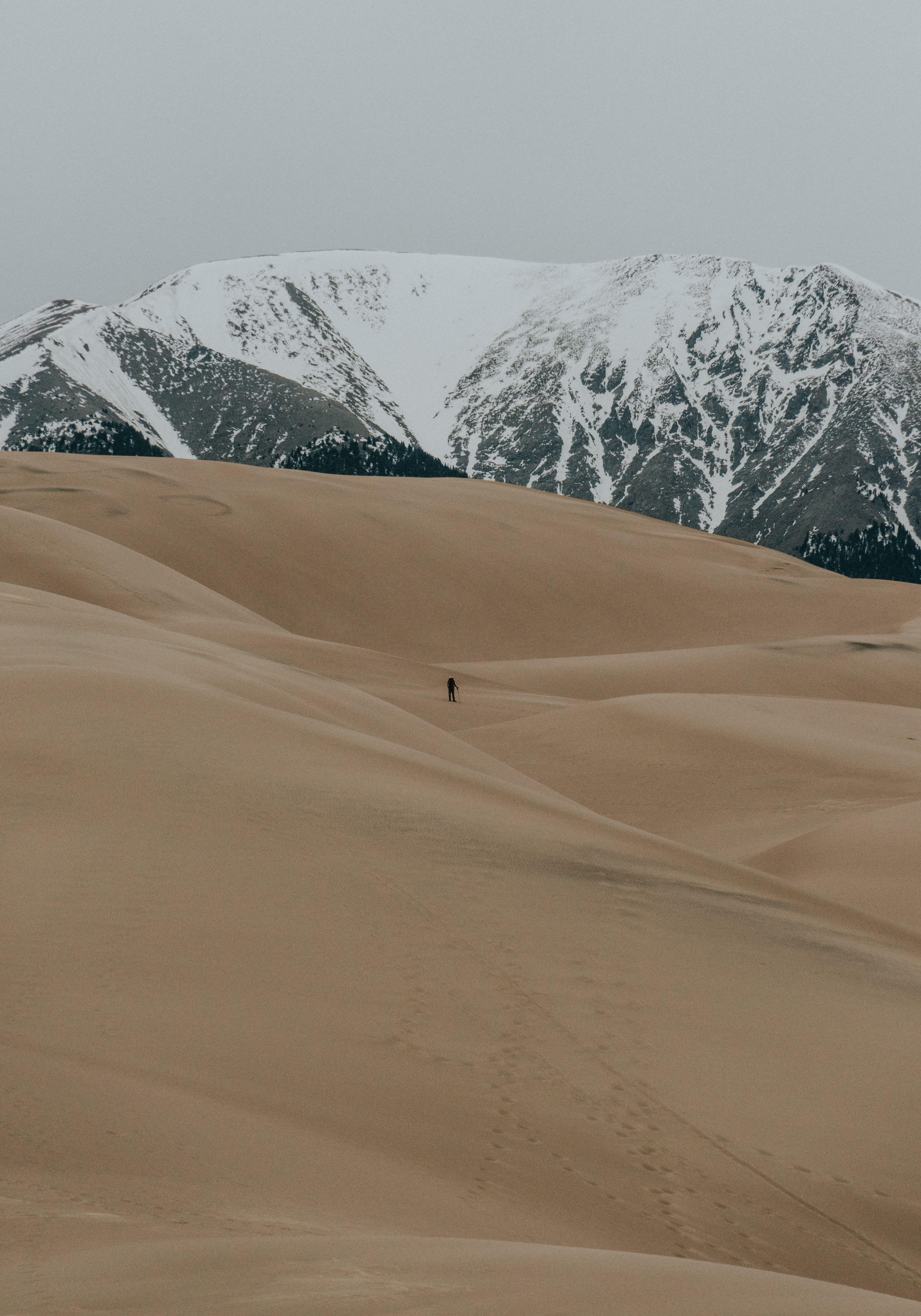 HD Wallpaper] The silhouette of a lone hiker among sand dunes with