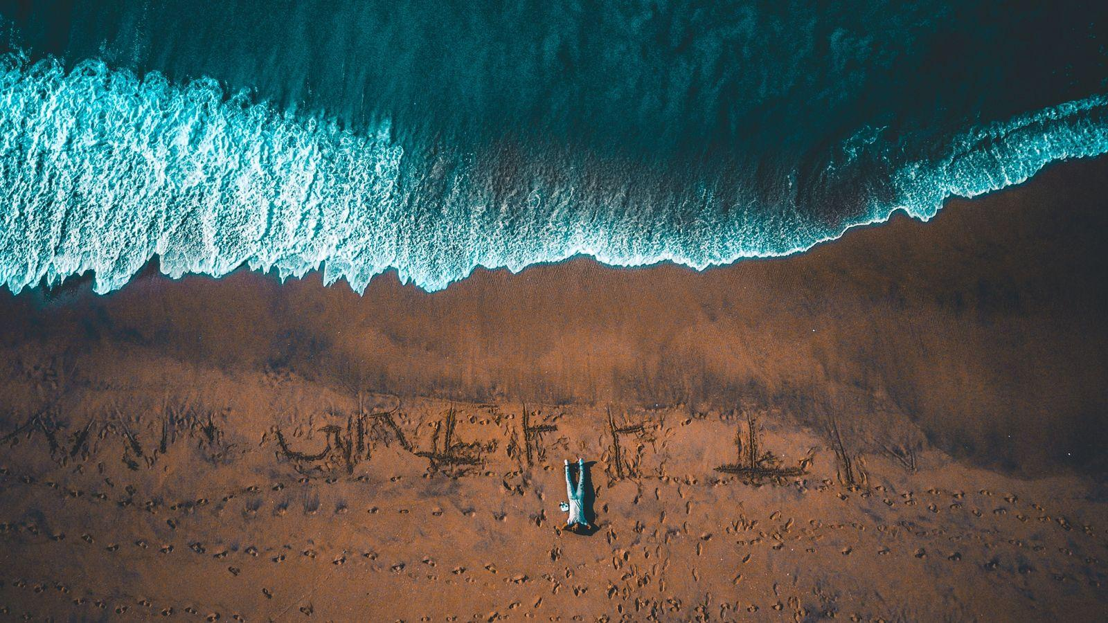 Download wallpapers 1600x900 man, ocean, view from above, shore, surf