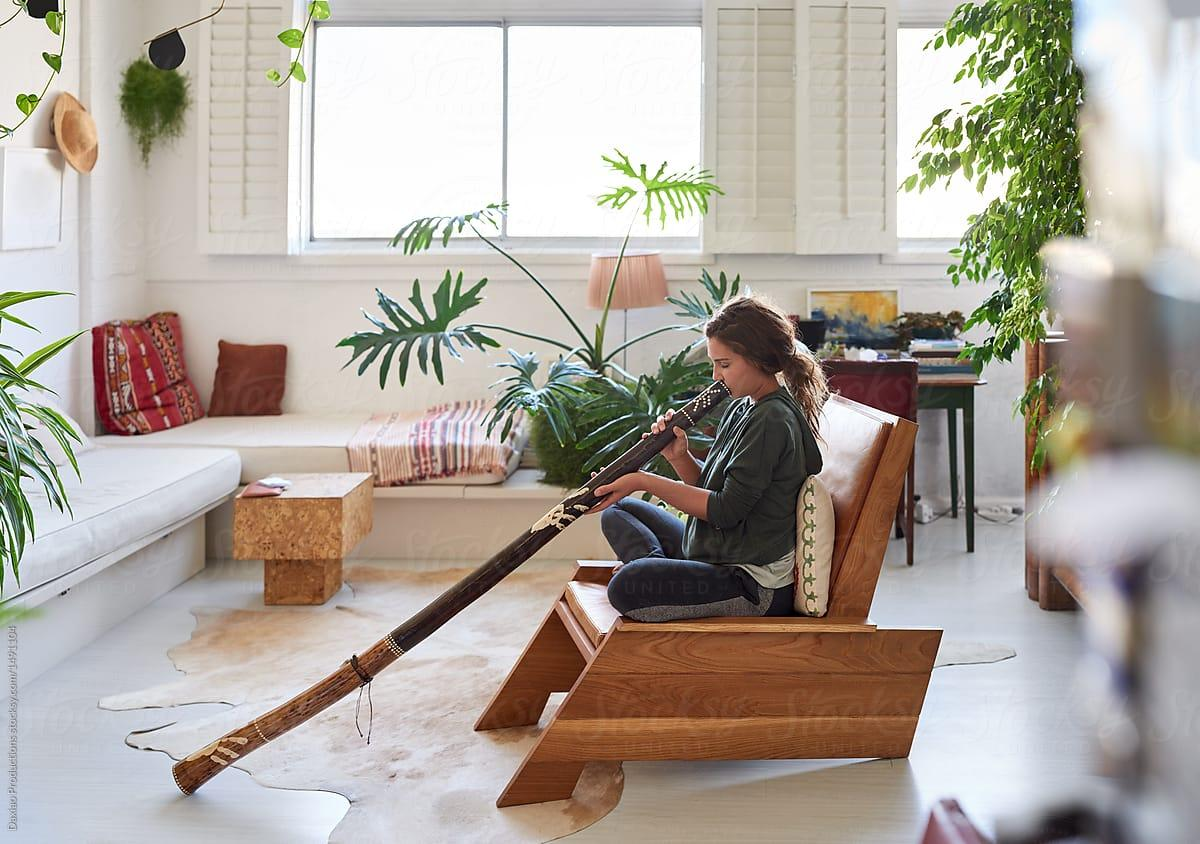 Hippy Woman Playing Didgeridoo At Home | Stocksy United