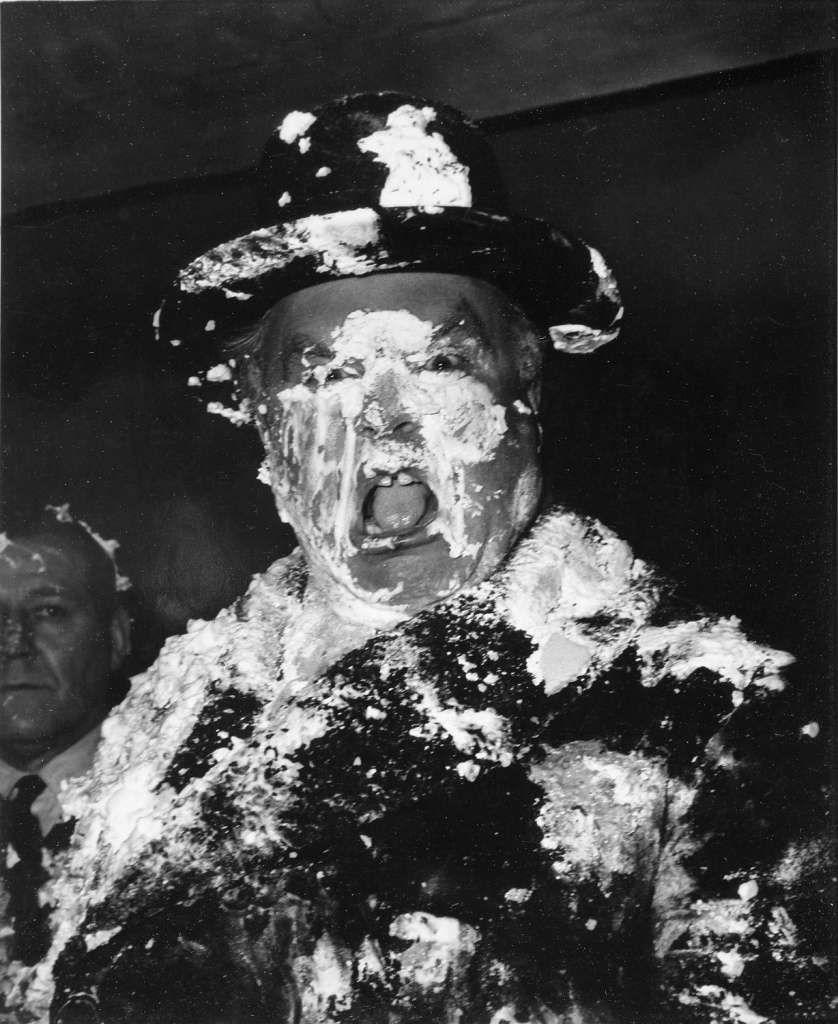 A man's face is covered in cream as a result of a pie fight in the