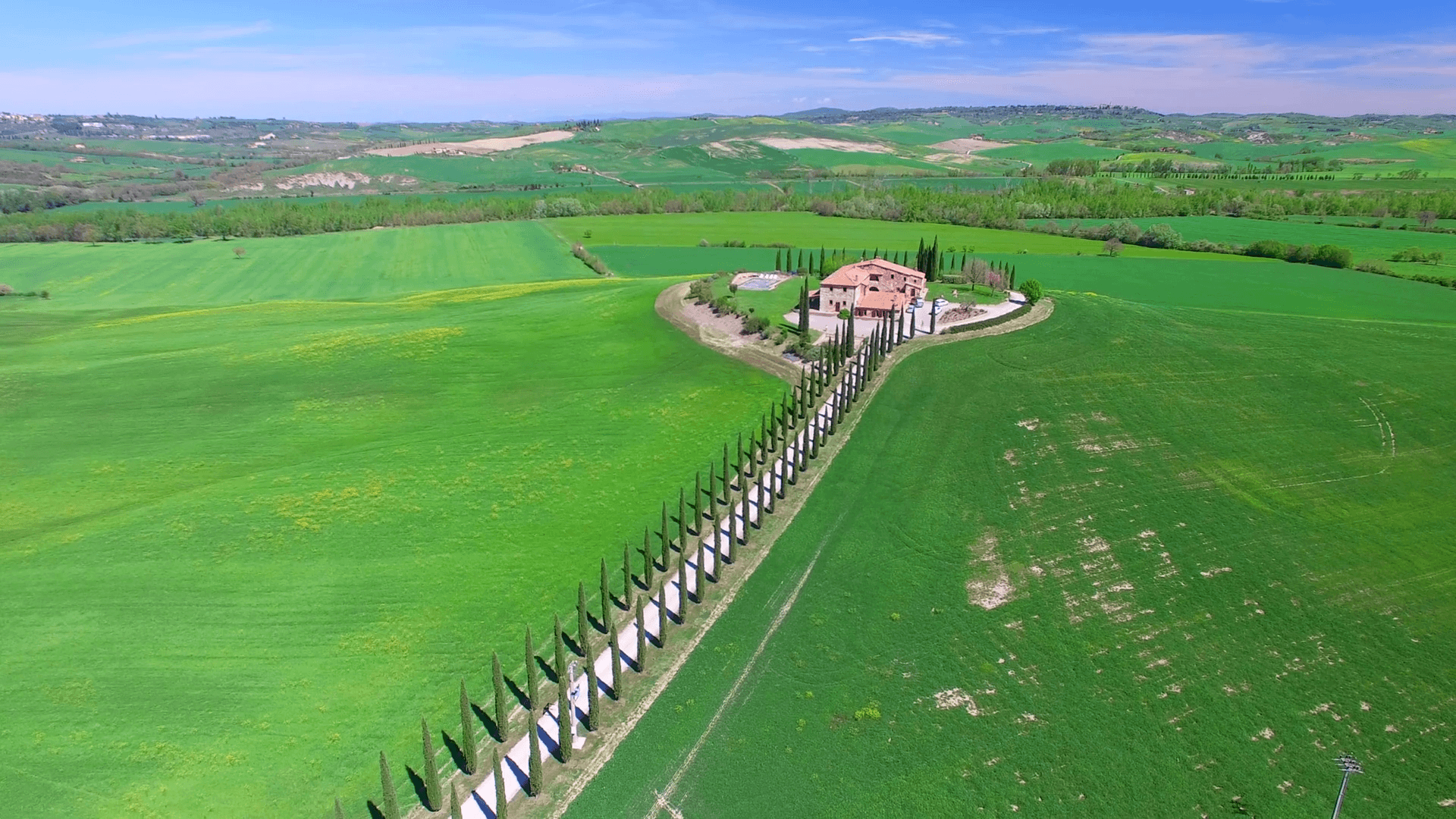 Aerial view of Tuscany countryside with cypresses and old house