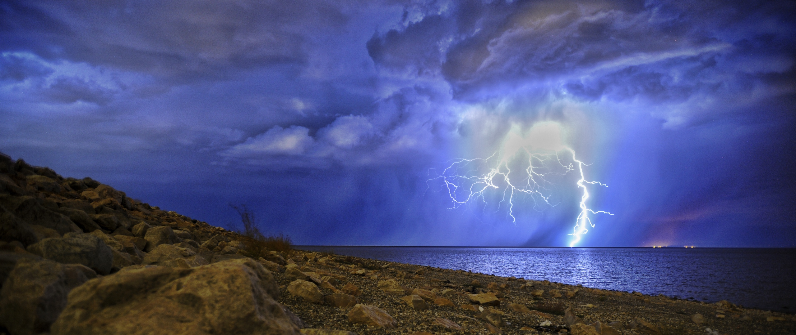 Download wallpapers 2560x1080 lightning, storm, lake, overcast, shore