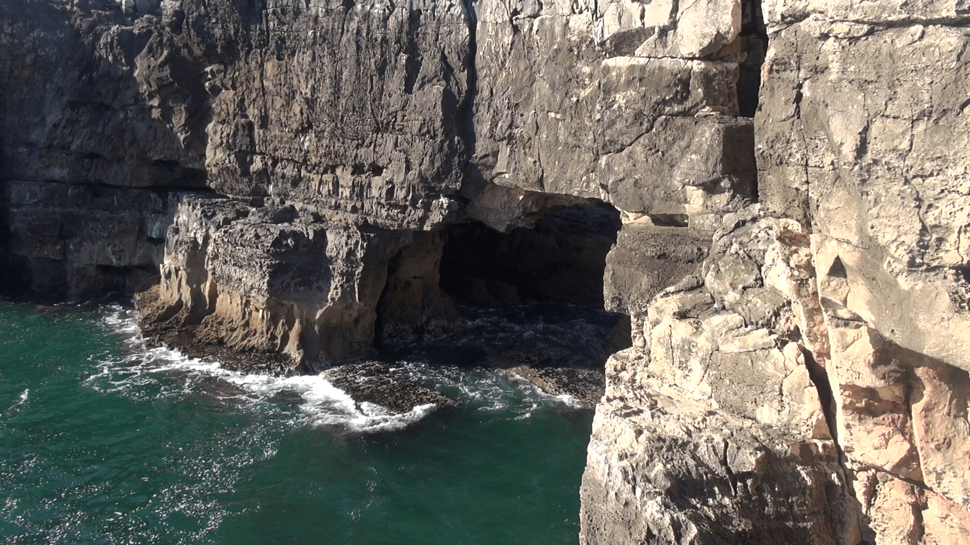 Rocky cliffs and cave over the water Stock Video Footage